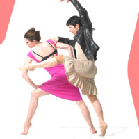 Two women pose in ballet positions: one woman leans on her left knee in a lunge with an arched foot, wearing a hot pink dress; the other leans on the first woman's shoulder in a front attitude in releve wearing a shiny beige dress and a black, leather jacket.