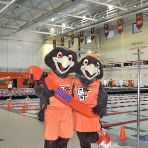 Freddie and Frieda Falcon holding a lifeguard rescue tube beside pool at Student Recreation Center
