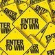 Enter to Win is written on yellow signs that are in a diamond shape like traffic signs. There are multiple signs piled up on each other in this image.