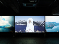 Three images projected as part of an installation by Soni Kum called, 'Morning Dew'. The left screen has clouds over a body of water. The central screen has a woman in traditional white clothes with a head covering of white as she stands with a deep blue lake in the background and a horizon of mountains. The right screen has blue mountains and a traditional Korean home nestled among them.