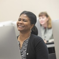 photo of a brown skinned woman smiling while sitting at a computer monitor