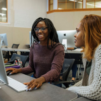 2 young Black women smiling in front of a computer monitor, one woman's hand is on the keyboard