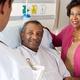 male patient smiling looking at doctor from hospital bed