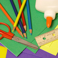 A bottle of glue, a ruler, a pair of scissors, and colored pencils sitting on top of several sheets of construction paper.