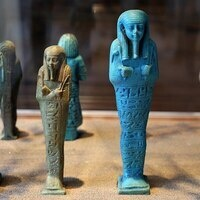 egyptian tan and blue ushabti figures covered in hieroglyphs