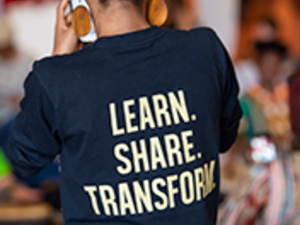 """The back of a person whose t-shirt reads: """"Learn. Share. Transform."""""""