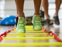 photograph of a pair of feet in tennis shoes doing an exercise in a ladder on the floor