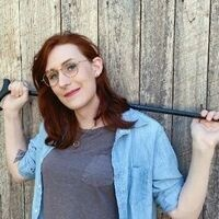 torrin a. greathouse posing with a cane propped behind her shoulders