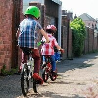 two children riding a bike in an alley