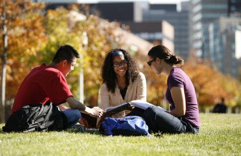 Three students sitting on lawn