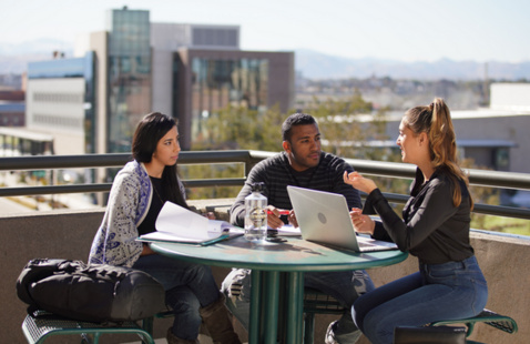 Three students sitting at table on rooftop