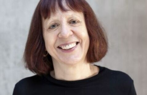 Close-up photo of Rita Felski. A smiling women with red, long-bob with bang hair and green eyes wearing a black sweater.