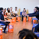 kids and an instructor tapping drumsticks on bucket drums