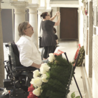 Three individuals, two wheelchair users, one standing and taking a photo in front of a wall with plaques and a wreath in front.