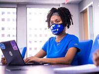 A student wearing a GSU mask works on her laptop in a sunlit classroom.