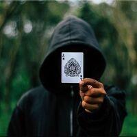 Magician Rhett Guter holding an Ace of Spades playing card