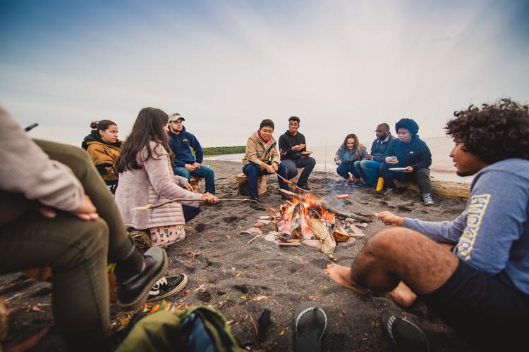 Student sitting around a fire.