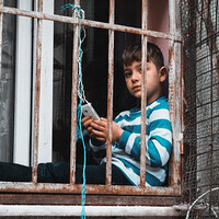 Photo of young boy sitting behind bars