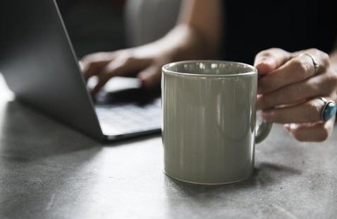 laptop and coffee mug at a virtual career fair