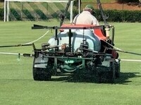 Commercial Pesticide Applicator Spraying a Sports Field