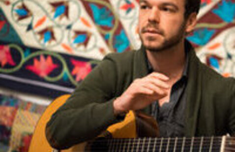 Adrian di Matteo in front a colorful tapestry with a guitar under one arm