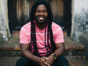 Dashon Burton '05 smiles into the camera. He is wearing a pink T-shirt with white stripes.