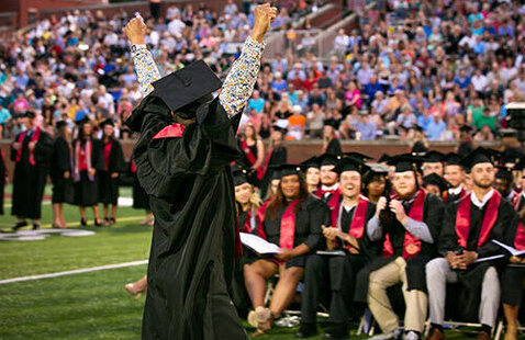 Student celebrates by raising arms at commencement