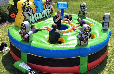 people playing giant human whack-a-mole on giant inflatable