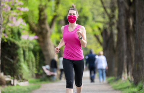 A young white woman is jogging outdoors, she has pink protective mask on face. She is running alone on a tree-lined road.