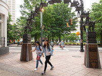 Students walk under an arched statue near Broad Street in downtown Atlanta