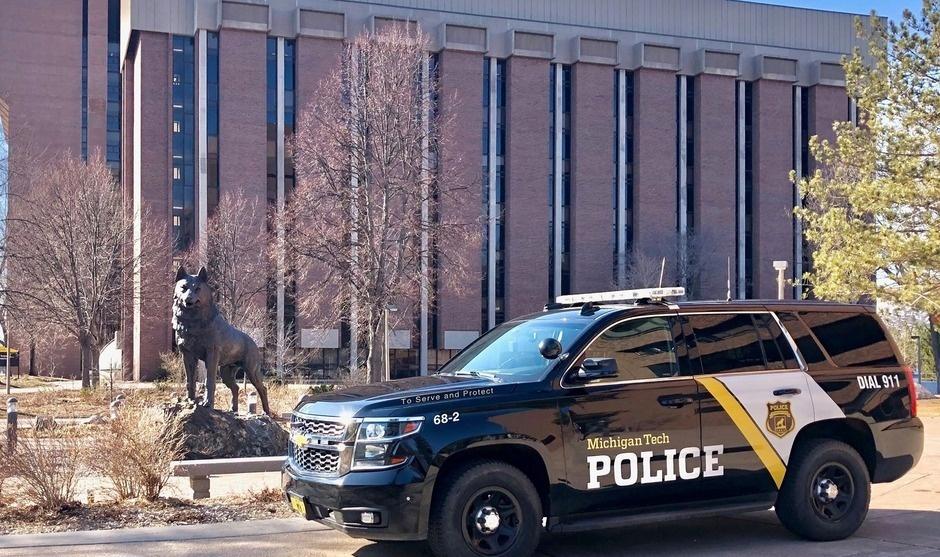 Michigan Tech Police Cruiser near the Husky Statue