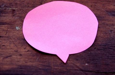 Pink speech balloon on wood background
