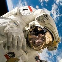 astronaut floating in space with Earth behind them