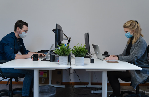 two workers in an office working on computers and wearing facemasks