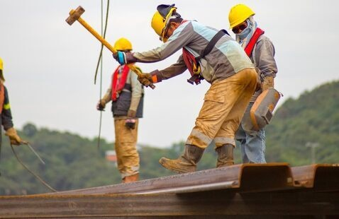 construction workers in hard hats and glasses with one holding a hammer