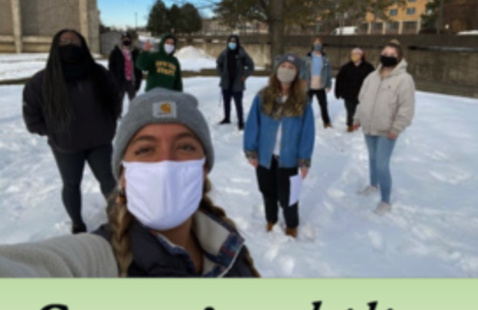 9 Sustainability office interns stand outside on campus by a maple tree. Snow is on the ground and they are socially distanced and wearing masks.