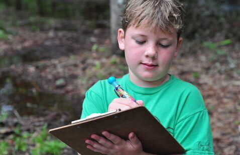 boy in green shirt with list and pen
