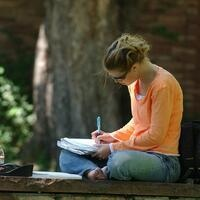 Women writing in notebook while sitting outside