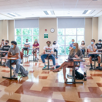 Masked students sitting in a socially distanced classroom.