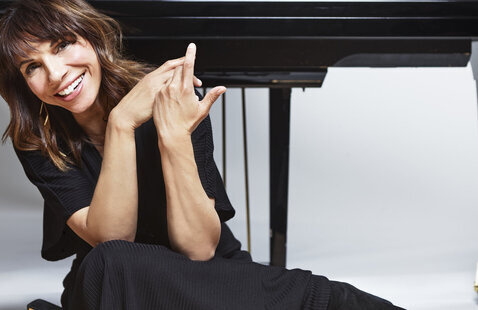 Lara Downes sitting cross-legged on the floor in front of a Yamaha grand piano, the key are facing us over her head, She is smiling, wearing a black dress with short sleeves and black boots.