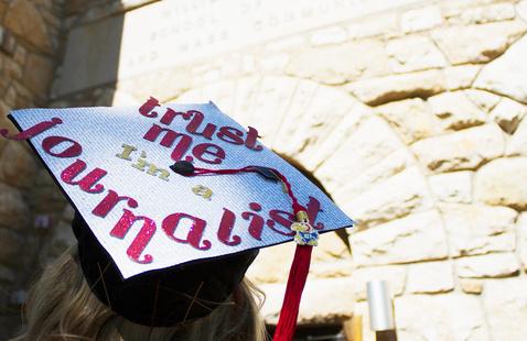 "Graduation cap that says ""Trust Me, I'm a Journalist."" Photo taken outside Stauffer-Flint Hall entrance"
