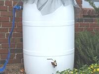 Rain barrel installed with a downspout