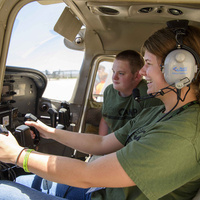 This picture has 2 students sitting in the cockpit of an airplane. They are both wearing green t-shirts and one is wearing a headset.