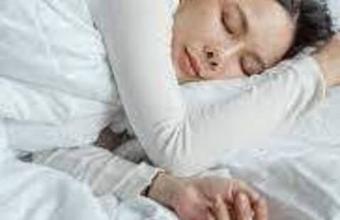 woman sleeping with cell phone next to hand