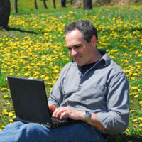 Person sitting in field of flowers working on laptop