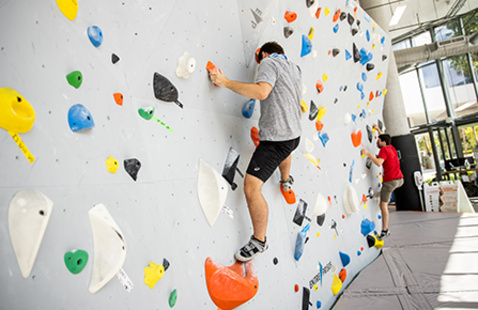 2 male students climbing on a bouldering wall