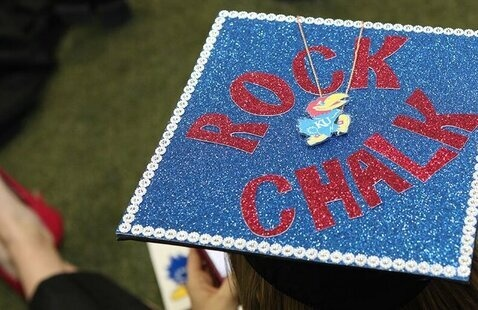 """Overhead shot of a graduation cap that says """"Rock Chalk"""" in red glittery letters against a blue glittery background with a Jayhawk in the center."""