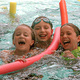Three young swimmers in the pool smiling for the camera and talking. The are using pool noodles and life jackets. The middle girl has clear and green goggles on her head.