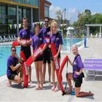 """A group of lifeguards posing together for the photo in front of one of the UREC outdoor lap pools. They are all holding their red """"guard"""" floaties. They all have on black shorts and a purple shirt."""