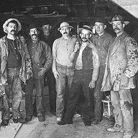 Group of miners standing in a group inside the opening of the entrance to a Nevada mine
